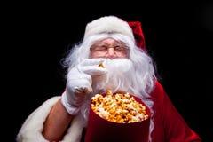 Jul Foto av Santa Claus den behandskade handen med en röd hink med popcorn, på en svart bakgrund Arkivfoton