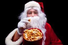 Jul Foto av Santa Claus den behandskade handen med en röd hink med popcorn, på en svart bakgrund Arkivfoto