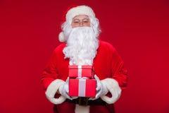 Jul Foto Santa Claus som ger xmas-gåva och ser kameran, på en röd bakgrund Royaltyfri Foto