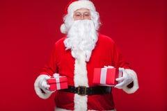 Jul Foto Santa Claus som ger xmas-gåva och ser kameran, på en röd bakgrund Fotografering för Bildbyråer