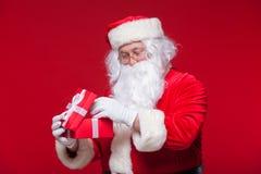 Jul Foto Santa Claus som ger xmas-gåva och ser kameran, på en röd bakgrund Arkivbilder