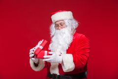 Jul Foto Santa Claus som ger xmas-gåva och ser kameran, på en röd bakgrund Arkivfoton