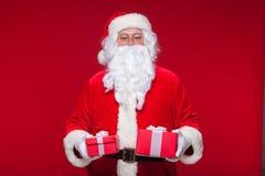 Jul Foto Santa Claus som ger xmas-gåva och ser kameran, på en röd bakgrund Arkivbild