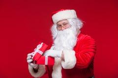 Jul Foto Santa Claus som ger xmas-gåva och ser kameran, på en röd bakgrund Royaltyfri Bild