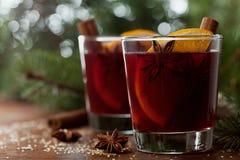 Jul funderade vin eller gluhwein med kryddor och apelsinskivor på den lantliga tabellen, traditionell drink på vinterferie, magis Royaltyfri Foto