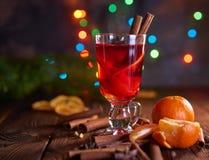 Jul funderade vin med apelsiner och kryddor med bokehljus Arkivbilder