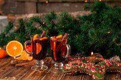 Jul funderade vin med frukter och kryddor på trätabellen Xmas-garneringar i bakgrund exponeringsglas två Vintervärmedrink r fotografering för bildbyråer