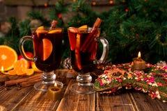 Jul funderade vin med frukter och kryddor på trätabellen Xmas-garneringar i bakgrund exponeringsglas två Vintervärmedrinkwi arkivbild