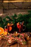 Jul funderade vin med frukter och kryddor på trätabellen Xmas-garneringar i bakgrund exponeringsglas två Vintervärmedrinkwi royaltyfri foto