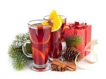 Jul funderade vin med kryddor, gåvaasken och det snöig granträdet Arkivfoto