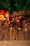 Jul funderat vin med frukter, stearinljus och kryddor på trätabellen Xmas-garneringar i bakgrund exponeringsglas två Vinterwarmin arkivfoto