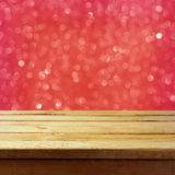 Jul gör sammandrag bakgrund med trätabellen, och röd bokeh blänker Royaltyfria Bilder