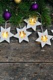 Jul gränsar: hemtrevliga varma ljusgirlandstjärnor och granfilialer på lantlig träbakgrund Top beskådar över handen arkivbilder