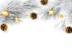 Jul gränsar med granfilialer, barrträdkottar, julbollar och guld- julprydnader på vit bakgrund Royaltyfria Bilder