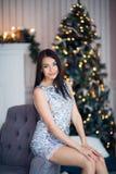 Jul Gullig flicka som bär hemmastatt sammanträde för skinande klänning på fåtöljen mot spis- och granträd royaltyfri fotografi