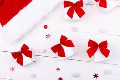 Jul hatt och gåvor, vita små askar med den röda pilbågen och godisar på vit träbakgrund Lekmanna- lägenhet glad jul Arkivbild