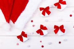 Jul hatt och gåvor, vita små askar med den röda pilbågen och godisar på vit träbakgrund Lekmanna- lägenhet glad jul Royaltyfri Fotografi