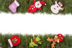 Jul inramar gjort av granfilialer som dekoreras med den isolerade snögubben och Santa Claus på vit bakgrund Arkivfoton