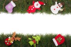 Jul inramar gjort av granfilialer som dekoreras med den isolerade snögubben och Santa Claus på vit bakgrund Arkivfoto