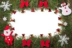 Jul inramar gjort av granfilialer som dekoreras med Santa Claus pilbågar, och isolerade klockor på vit bakgrund Royaltyfri Bild