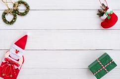 Jul inramar gjort av jul krans, röd socka för jul, den santa dockan och lantliga beståndsdelar för gåvaask på det vita wood bräde arkivbilder