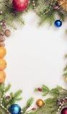 Jul inramar med julprydnader och garneringar tangerin kryddnejlikor Arkivfoton