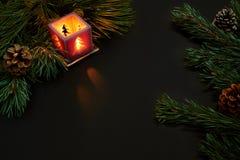 Jul, julträd, stearinljus, kottar och kanelbruna pinnar på svart bakgrund Arkivfoton