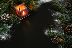 Jul, julträd, stearinljus, snö, kottar och kanelbruna pinnar på svart bakgrund Arkivbilder