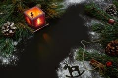 Jul, julträd, stearinljus, snö, kottar och kanelbruna pinnar på svart bakgrund Arkivfoto