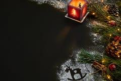 Jul, julträd, stearinljus, snö, kottar och kanelbruna pinnar på svart bakgrund Arkivbild