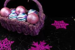Jul klumpa ihop sig i purpurfärgad korg på svart bakgrund dekorativa snowflakes Royaltyfri Fotografi