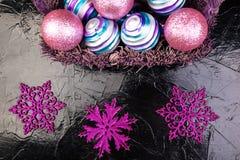 Jul klumpa ihop sig i purpurfärgad korg på svart bakgrund dekorativa snowflakes Royaltyfria Foton