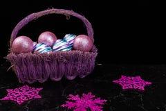 Jul klumpa ihop sig i purpurfärgad korg på svart bakgrund dekorativa snowflakes Royaltyfria Bilder
