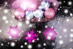 Jul klumpa ihop sig i purpurfärgad korg på svart bakgrund dekorativa snowflakes Royaltyfri Bild