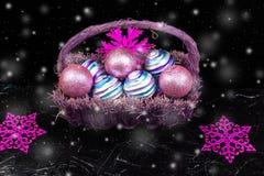 Jul klumpa ihop sig i purpurfärgad korg på svart bakgrund med snö dekorativa snowflakes Arkivfoto