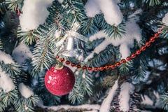 Jul klumpa ihop sig, och en klocka på täckt snö förgrena sig royaltyfri foto
