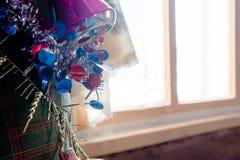 Jul klumpa ihop sig på trädet i den ljusa fönsterbakgrunden med andra garneringar och girlander kopiera avstånd Arkivbild