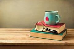 Jul kopp te och böcker på trätabellen med kopieringsutrymme Arkivbild
