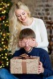 Jul kopplar ihop, den lyckliga unga kvinnliga överraskningmanräkningen hans ögon Arkivbild
