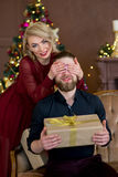 Jul kopplar ihop, den lyckliga unga kvinnliga överraskningmanräkningen hans ögon Arkivfoton