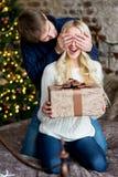 Jul kopplar ihop, den lyckliga unga kvinnlign som förvånas av mannen, täcker henne Arkivbilder