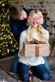 Jul kopplar ihop, den lyckliga unga kvinnlign som förvånas av mannen, täcker henne Royaltyfri Fotografi