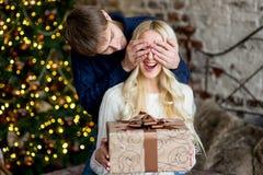 Jul kopplar ihop, den lyckliga unga kvinnlign som förvånas av mannen, täcker henne Royaltyfri Bild