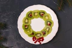 Jul krans, mellanmål av kiwin och granatäpple, idérik matkonstidé arkivfoto