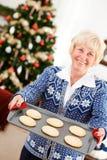 Jul: Kvinna som rymmer Tray Of Christmas Cookies Arkivbild