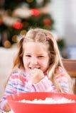 Jul: Lilla flickan äter något popcorn som betyds för trädgirland royaltyfria bilder
