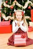 Jul: Lilla flickan hoppas för special feriegåva royaltyfria foton