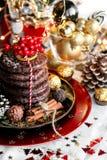 Jul ljust rödbrun bröd för xmas med rönnen, bergaska och sötsaker, kakor på den röda plattan, guld- bollar och konfettier med kan royaltyfri fotografi