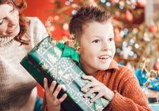Jul lycklig familj, son och moder som packar upp gåvor royaltyfria foton