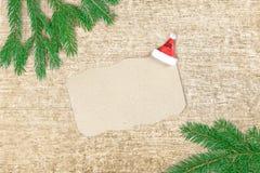 Jul märker till Santa Claus Granfilialer och ark av papper med garneringar på den gamla träbakgrunden Fotografering för Bildbyråer